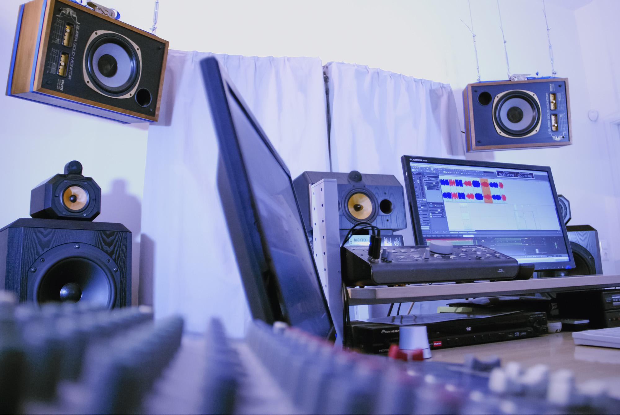 Das Tonstudio Artis Mastering von Robert Eder in Wien, sein Arbeitsplatz aus schräger Perspektive mit Mischpult, B&W-Boxen, Computer, violett-blau beleuchtet